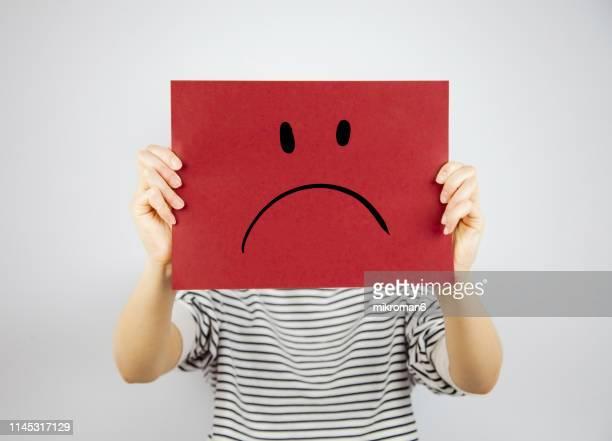 woman showing a paper page with a sad face - raiva emoção negativa - fotografias e filmes do acervo