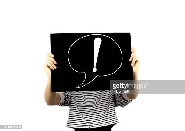 woman showing a paper page with exclamation point in a speech bubble - placard stock pictures, royalty-free photos & images