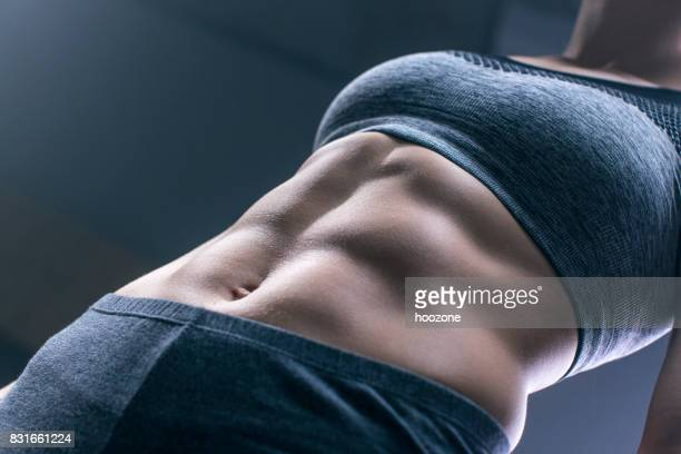 woman showing abdominal muscles - perfect female body shape stock photos and pictures