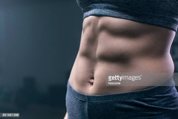 woman showing abdominal muscles - female navel stock photos and pictures