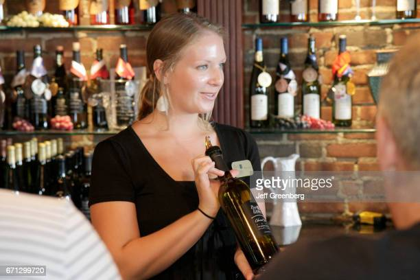A woman showing an estate bottled wine in the Brys Estate vineyard boutique winery tasting room