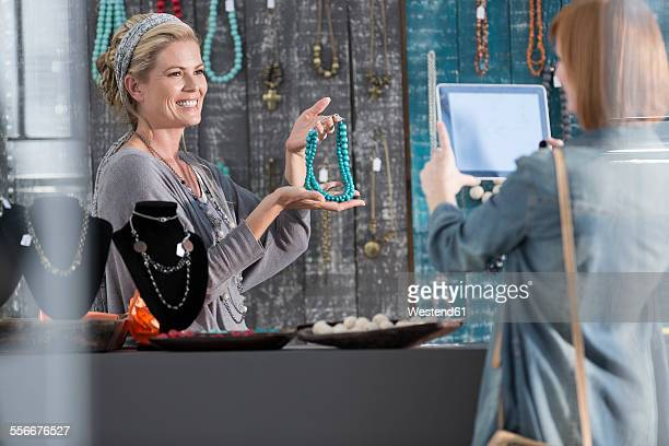 woman showing bead necklace to a customer taking pictures with a tablet - jewellery products stock photos and pictures