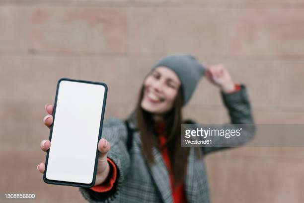 woman showing blank smart phone screen against wall - demonstration stock pictures, royalty-free photos & images
