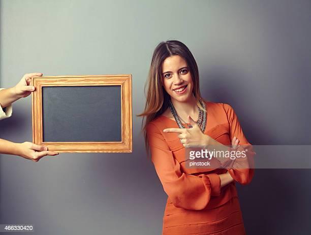 woman showing board in front of the wall. - bord bericht stockfoto's en -beelden