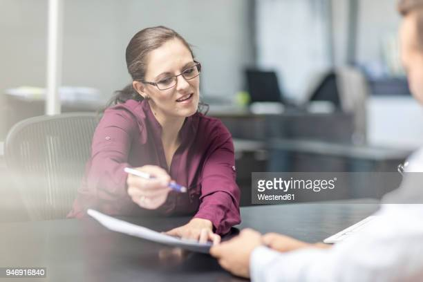 woman showing contract to client at desk - accountant stock photos and pictures