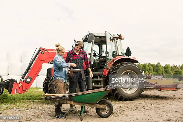 Woman showing document to male worker by tractor at farm