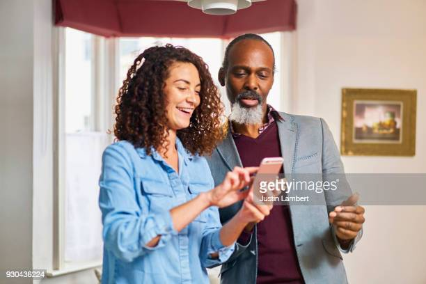 woman showing family member something on their phone at home - uncle stock photos and pictures