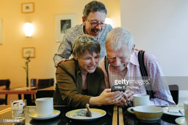 woman showing father and his partner photos on smartphone - women in suspenders stock pictures, royalty-free photos & images