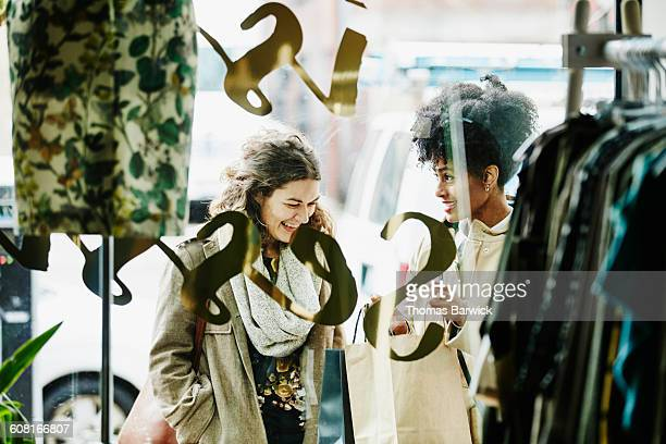 Woman showing friend items in shopping bag