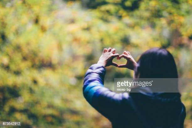 Woman Showing Heart Shape To Nature
