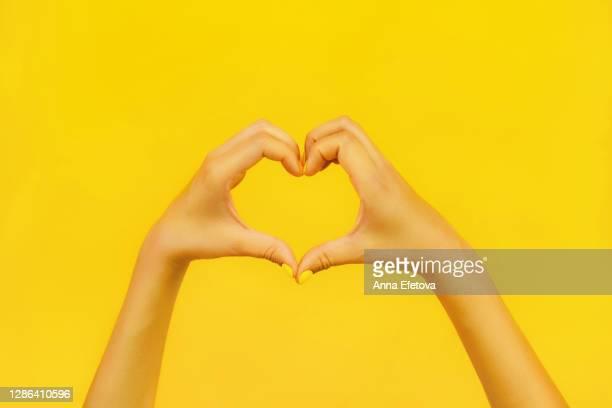 woman showing heart sign with fingers. trending bright background of the year. charity concept. - menselijk lichaamsdeel stockfoto's en -beelden
