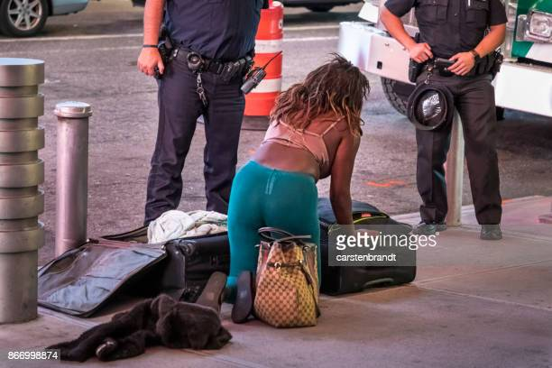 woman showing her belongings to the police - belongings stock photos and pictures