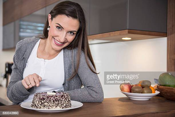 Woman showing her cake in a kitchen and smiling, Munich, Bavaria, Germany