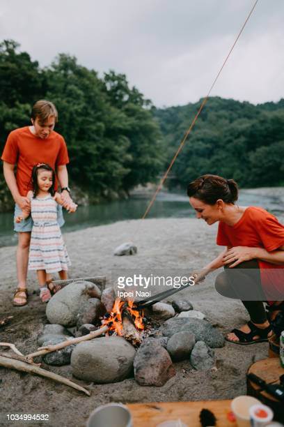 Woman showing her child how to make campfire by river, Japan