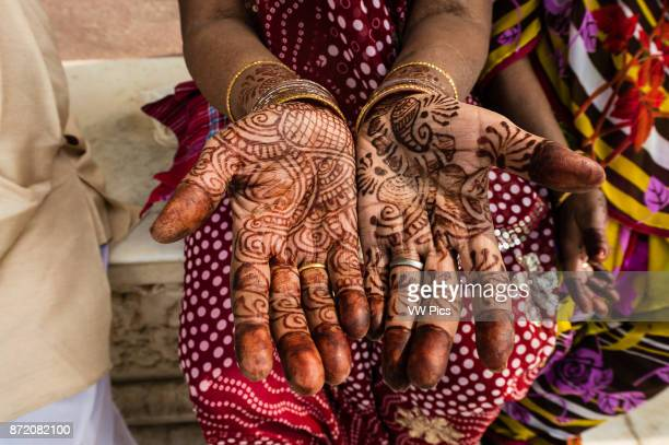 A woman showing her henna tattoed hands