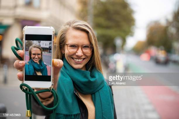 woman showing her selfie on her phone to camera - showing stock pictures, royalty-free photos & images