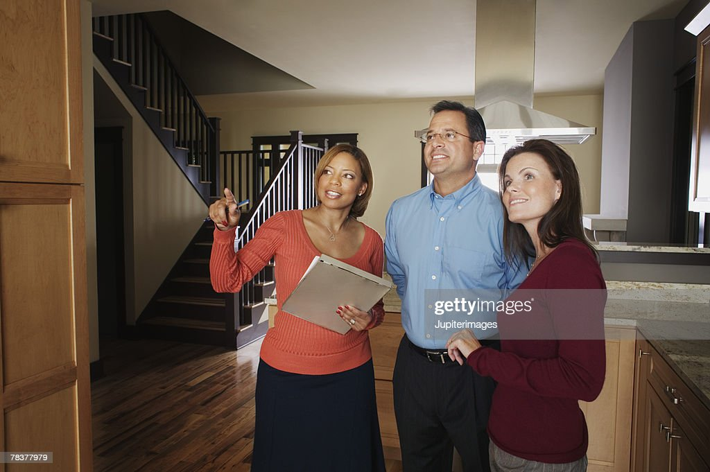 Woman showing house to couple : Stock Photo