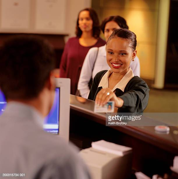woman showing identification card to teller in bank - id card stock pictures, royalty-free photos & images