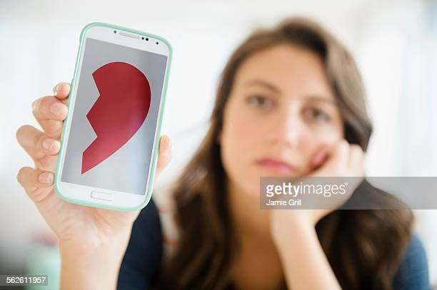 woman showing image of broken heart on her smartphone - online dating stock pictures, royalty-free photos & images