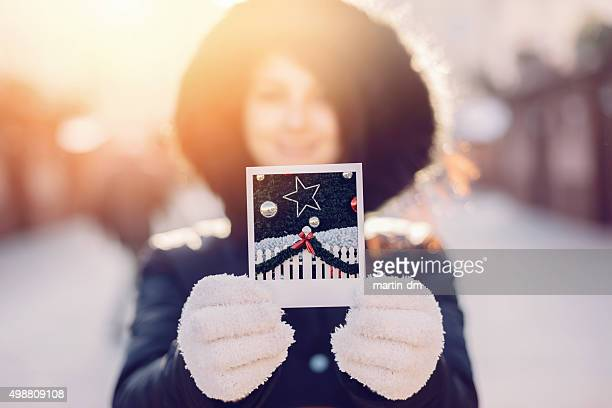 Woman showing instant photo of Christmas tree
