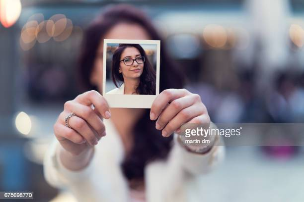 Woman showing instant photo to the camera