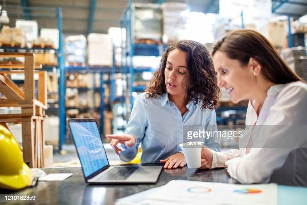 woman showing inventory on laptop to warehouse manager - distribution warehouse stock pictures, royalty-free photos & images