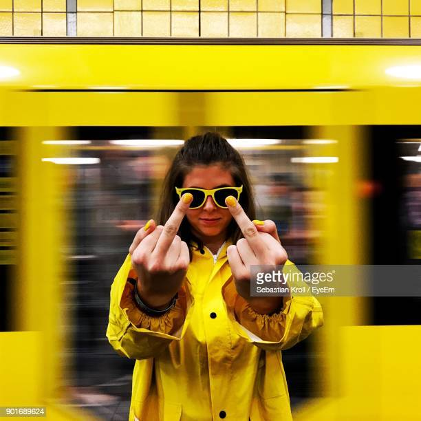 Woman Showing Middle Finger Against Yellow Light Trail