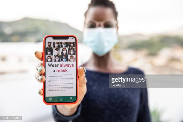 mulher mostrando tela de celular com notícias relacionadas ao covid-19 - exposição - fotografias e filmes do acervo