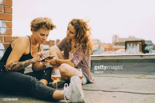 woman showing mobile phone to friend while sitting on terrace during rooftop party - 女の友情 ストックフォトと画像