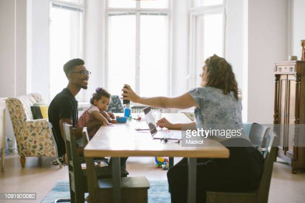 woman showing mobile phone to man sitting with daughter at table in house - house icon stock pictures, royalty-free photos & images