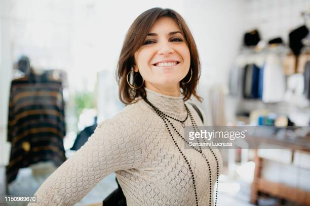 woman showing off necklace in fashion boutique - showing off stock pictures, royalty-free photos & images
