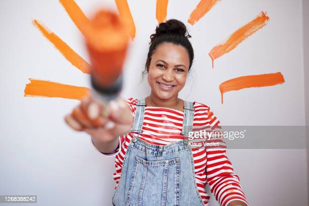 woman showing paintbrush against wall - focus on background stock pictures, royalty-free photos & images