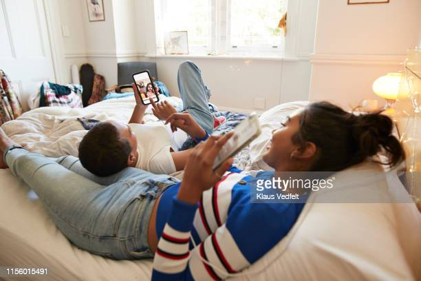 woman showing photograph to friend through smart phone - photo messaging stock pictures, royalty-free photos & images
