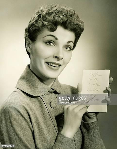 Woman showing shopping list in studio, (B&W), portrait