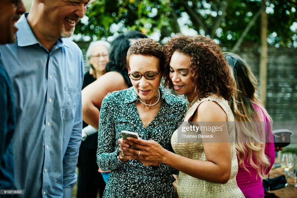Woman showing sister inlaw photos on smartphone after outdoor family dinner party : Stock Photo