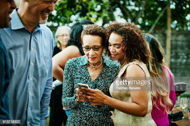Woman showing sister inlaw photos on smartphone after outdoor family dinner party