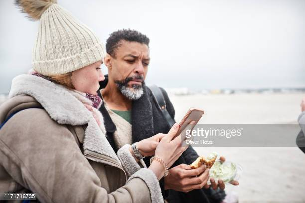 woman showing smartphone to man on the beach - showing stock pictures, royalty-free photos & images