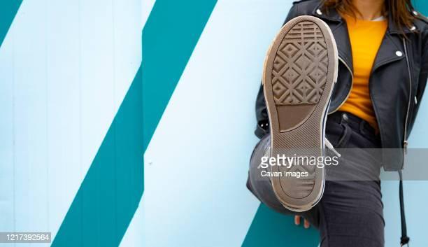 woman showing the sole of her sneaker on a blue background. - donner un coup de pied photos et images de collection