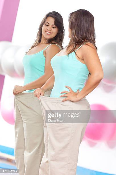 woman showing weight loss succes with big pants
