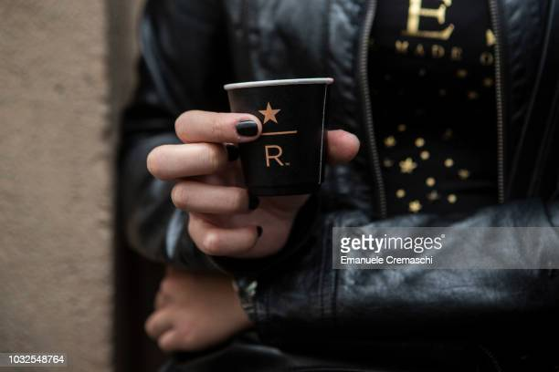 A woman shows a branded coffee cup during the opening of Europe's largest and Italy's first Starbucks Reserve Roastery located inside a historic post...
