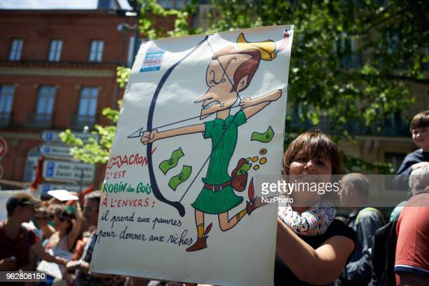 A woman shows a drawing depicting Macron as Robin Hood It reads 'Macron is a Robin Hood the other way round he took to workingclass to give to richs'...