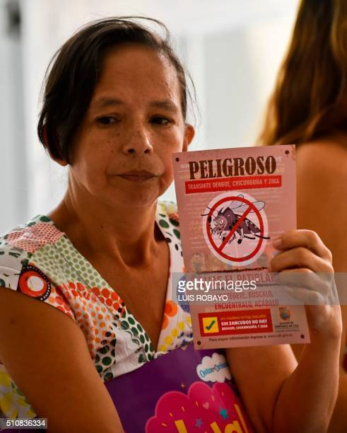 Woman shows a leaflet with information on the Aedes aegypti mosquito on February 17 in Cali, Colombia. Cali's Health Secretariat massively delivered...