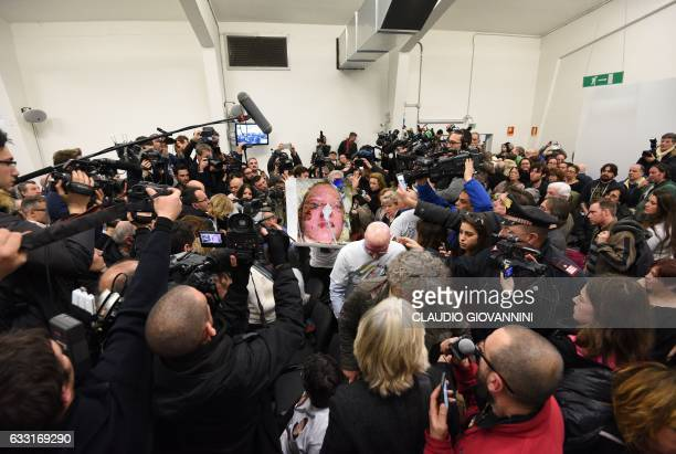 A woman shows a photo of her daughter in hospital during the trial of the rail disaster of Viareggio that killed 32 people in 2009 after the...