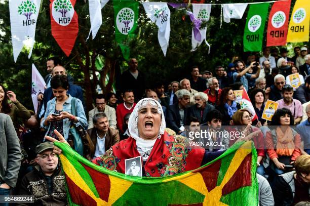 Woman shows a photo of Selahattin Demirtas, former leader of the pro-Kurdish Peoples' Democratic Party HDP, in jail for a year and a half, and HDP...