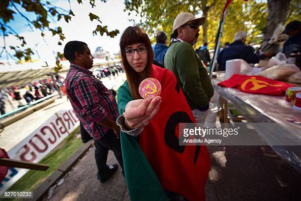 A woman shows a pin of the Communist Party of Uruguay in the act for Labor Day in Montevideo on May 1 2016