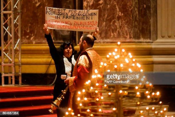 A woman shows a poster reading 'Freedom for all political prisoners in Armenia' during a joint ecumenical service of German and Oriental Orthodoxy...