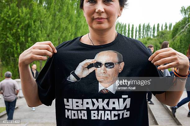 Woman shows a shirt with the face of Vladimir Putin on Victory Day, when Nazi Germany surrendered to the Soviet Union at the Soviet war cemetery and...