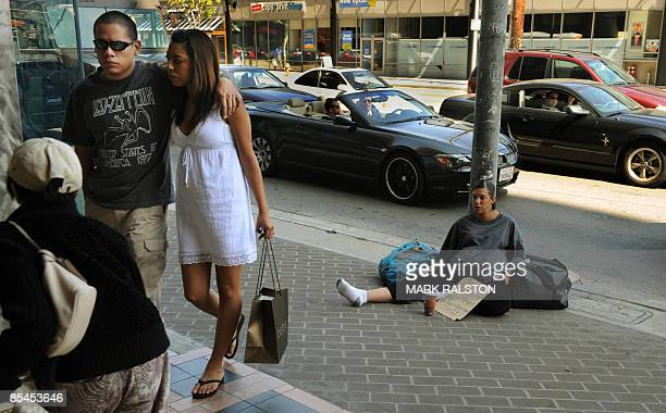 """Woman shows a sign saying """"Please Help, Pregnant, Hungry and Homeless"""" as she begs for money near Beverly Hills in Los Angeles on March 16, 2009...."""