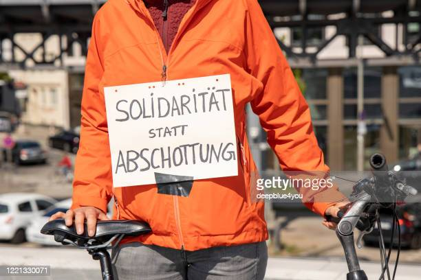 """woman shows a sign that reads """"""""solidarität statt zwangsvollstreckung"""" in the city of hamburg - anti racism stock pictures, royalty-free photos & images"""