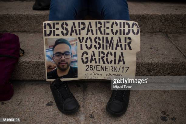 A woman shows a sign with the image of his missing relative during a march on Mother's Day on May 10 2017 in Mexico City Mexico Mothers whose...